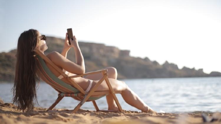 mujer en la playa con el movil