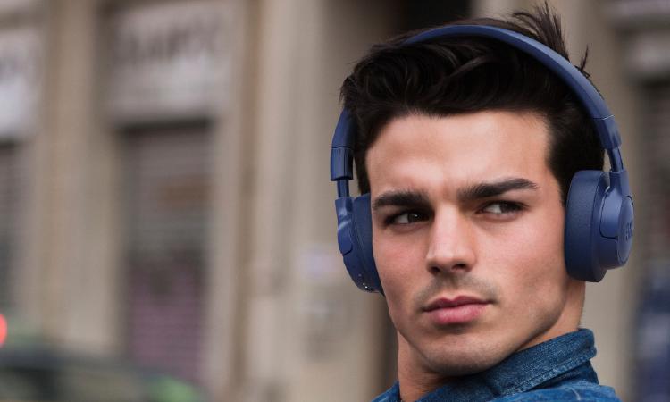 chico con auriculares bluetooth azules
